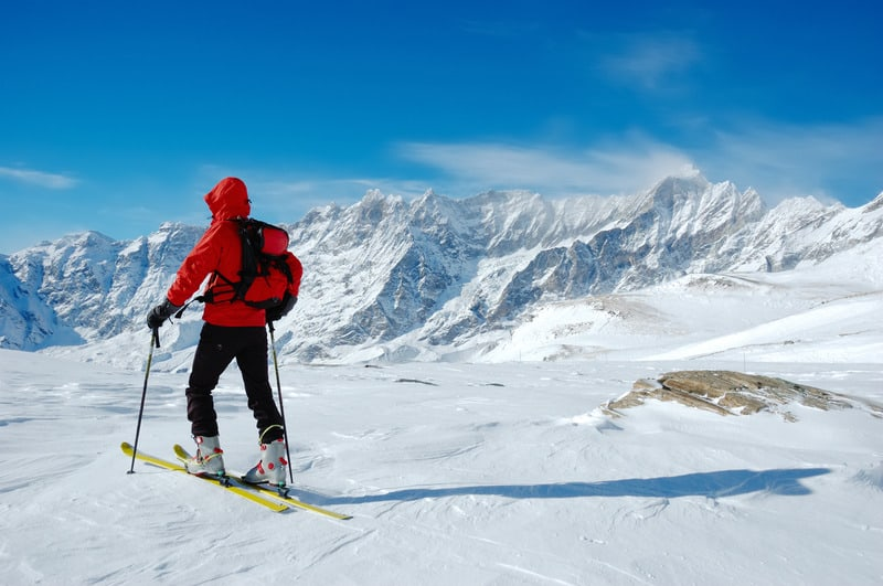 A lonely backcountry skier in a sunny winter day, alpine scenic, skiing in liechtenstein