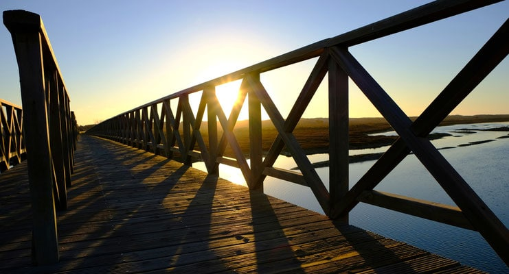 winter holidays in algarve, winter sun peaking out through wooden bridge