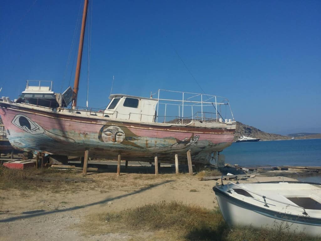 where to go in paros, old boats on the water, one has artwork of woman holding moon and eye on the side