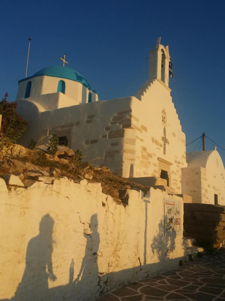 things to do in paros,greece, shadow on building at sunset of two people talking