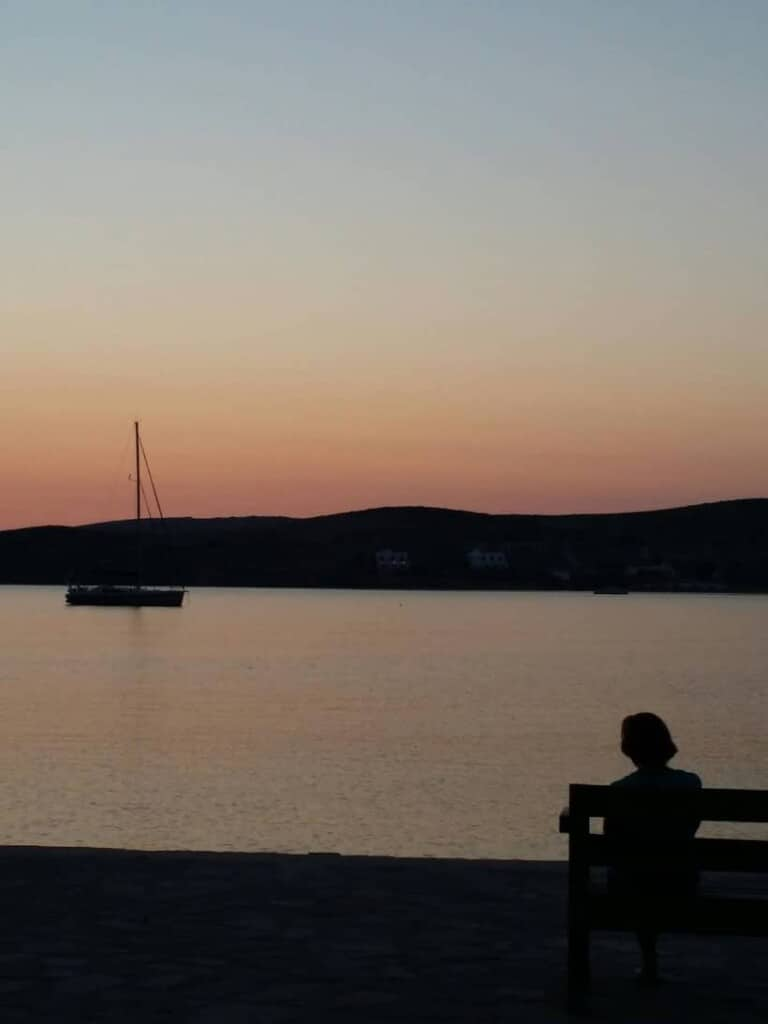 must see things in paros, person on bench watching boat in the sea at sunset