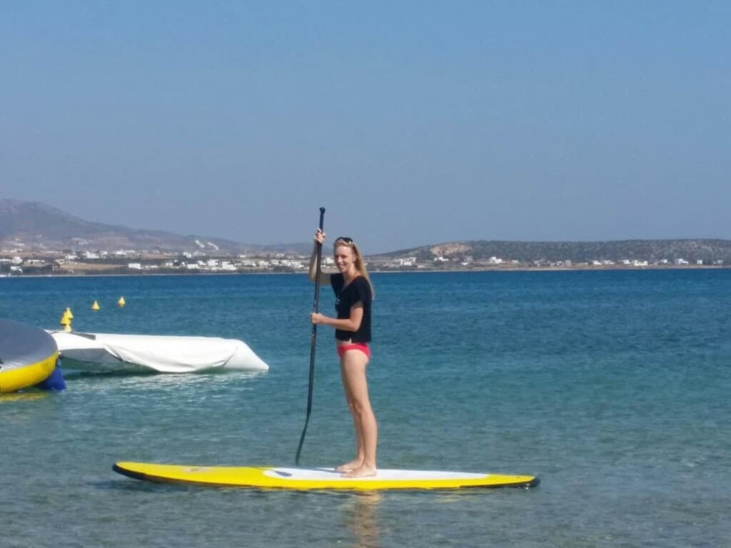 fun things to do in paros island, standing on a SUP kayak in the water