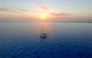 boat hitch hiking, catamaran on the ocean at sunset, discover the world, sailing blog