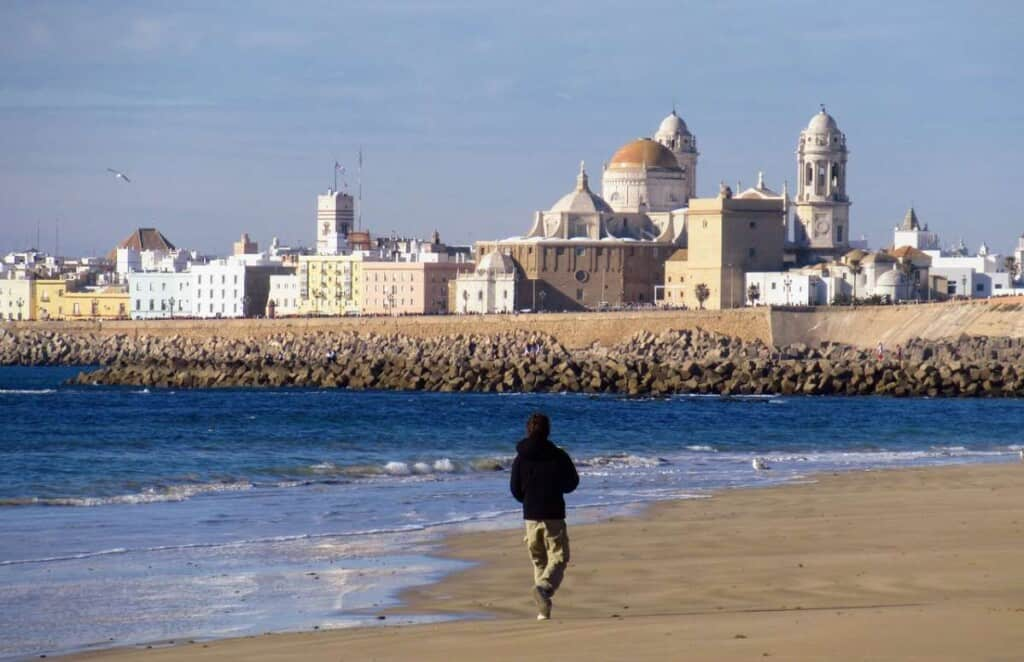 travel from malaga to cadiz, man walking along the coast in cadiz