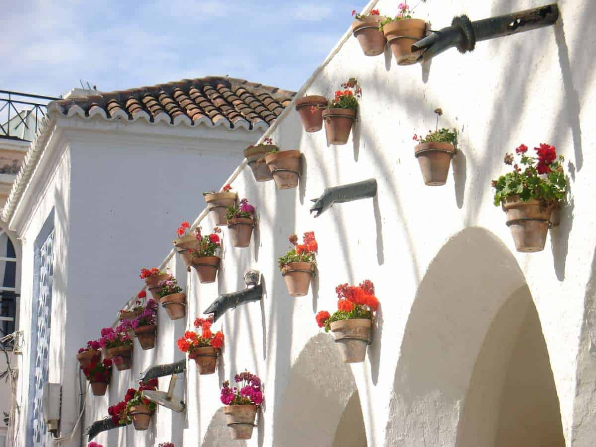 best day trips from malaga spain, flower pots hanging on a wall in frigiliana