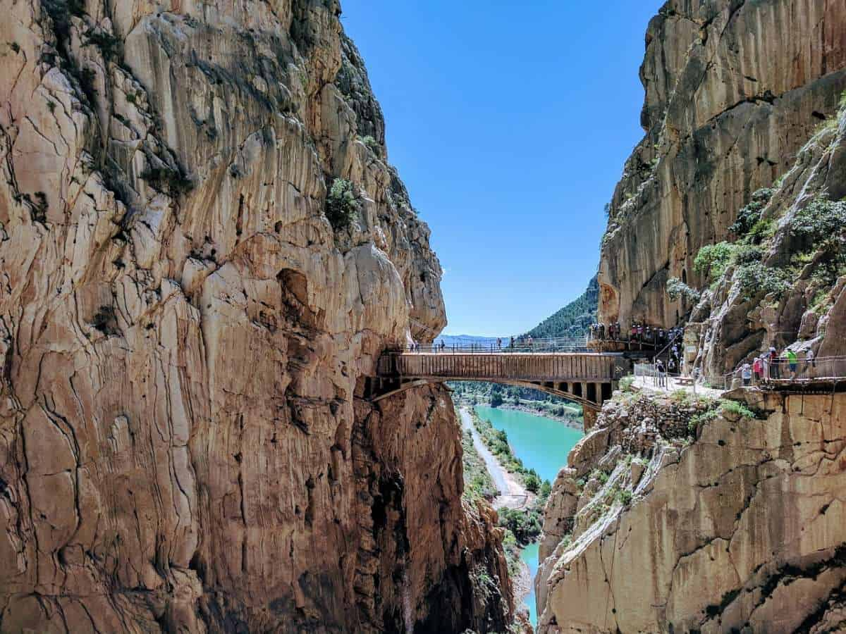 places to visit near malaga, tourists crossing the caminito del rey