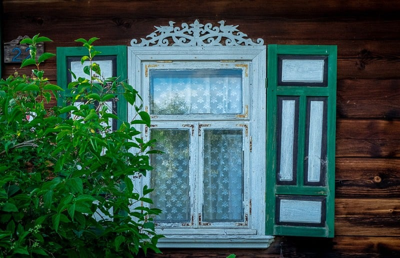 window in podlaskie, poland, near bialowieza forest with colorful shutters, things to do in bialowieza forest, girl hiking in bialowieza forest