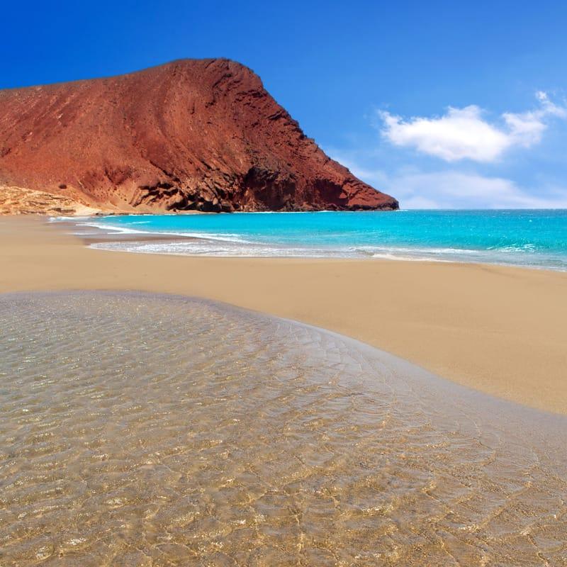 Beach Playa de la Tejita turquoise in Tenerife Canary islands with red mountain