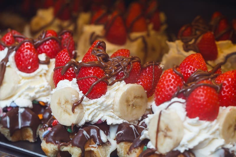 Belgian waffles with whipped cream, chocolate and strawberries on the display case