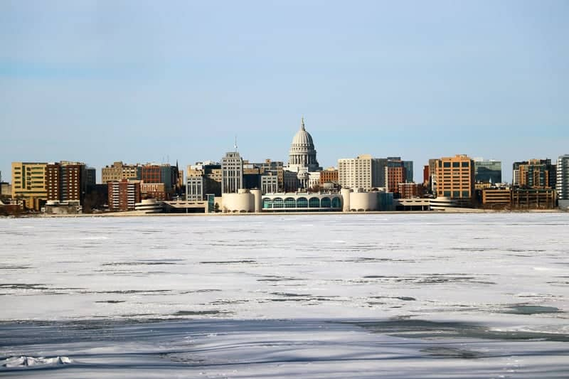 Madison winter cityscape with frozen lake Monona on a foreground during cold sunny day. Midwest USA, Wisconsin.