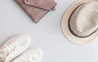Flat lay travel items - shoes, hat and purse on grey background