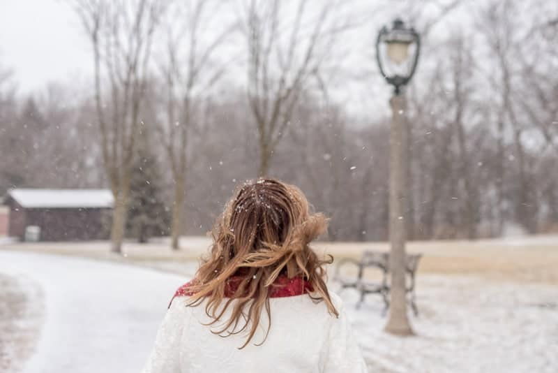 rear view of woman walking in park in winter with hair blowing in wind and magical snow falling