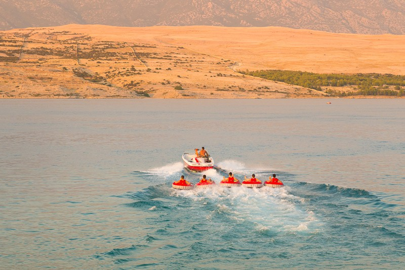 Kids tube riding tawed by speedboat on Croatian coast. Summer sea fun and adventure. Exciting water sport. tenerife, spain, watersports