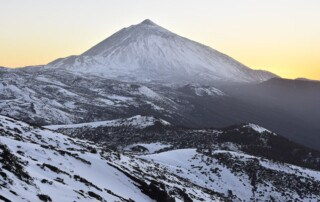 Pico del Teide at dusk - 3718 m high mountain and volcanic landscape of Teide National Park covered with snow. Tenerife Canary Islands Spain.