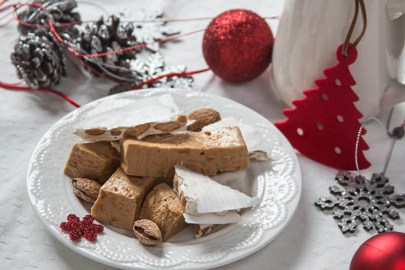 Typical dessert for Christmas, spanish turron served in white plate and background