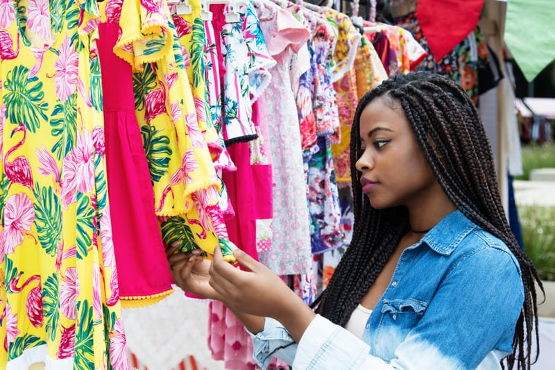 African american woman shopping colorful clothes outdoors at typical traditional market, cabo verde, cape verde holidays, vacation, travel