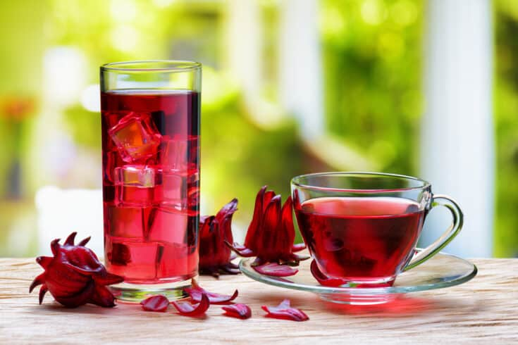 Cup of hot hibiscus tea (karkade, red sorrel, Agua de flor de Jamaica) and the same cold drink with ice cubes in glass on wooden table. Drink made from magenta calyces (sepals) of roselle flowers.