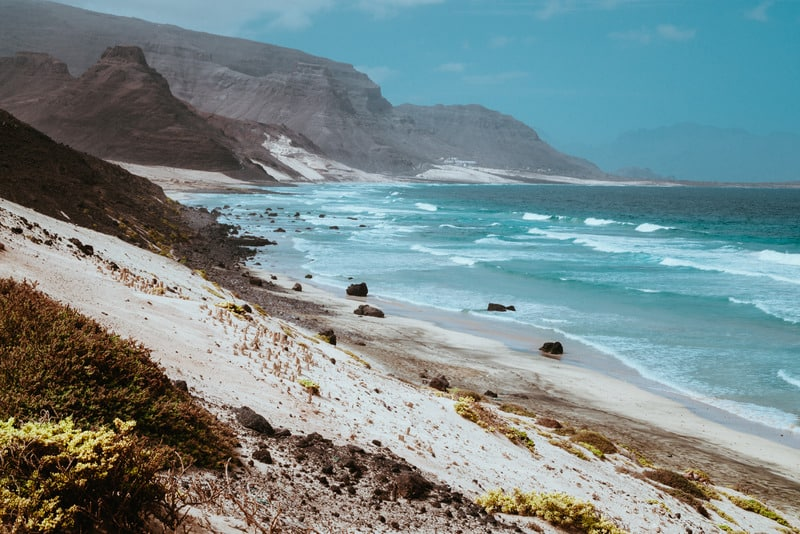 things to do in sao vicente, ravel to sa vicente, cabo verde, cape verdeStunning view over barren rugged volcanic cliffs and sand dunes. Vast plain of the coastline. Baia Das Gatas. North of Calhau, Sao Vicente Island Cape Verde.