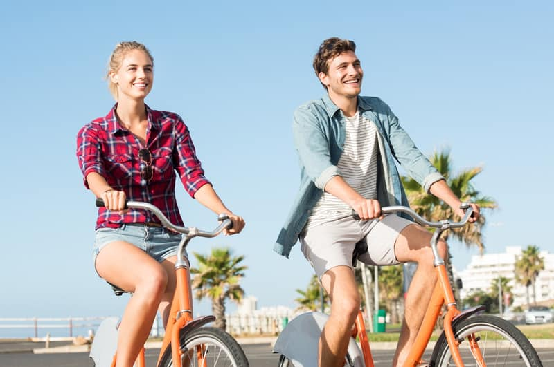 Staycation Ideas, Active young couple riding bikes during summer vacation.