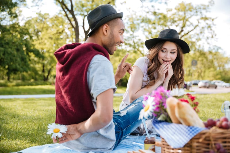 Staycation Ideas for Couples, Couple having picnic in park with some tasty finger foods and fruit.