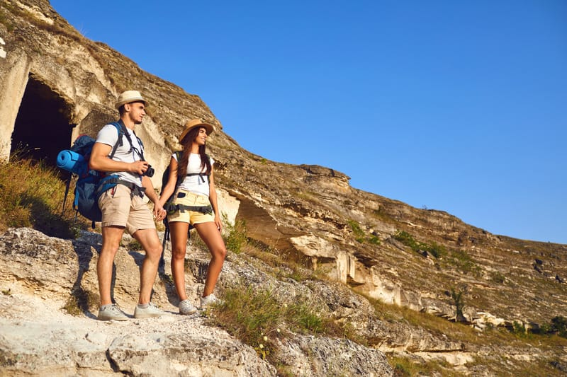 Staycation Ideas for Couples, Happy hiking couple with backpack On a hike in mountains.