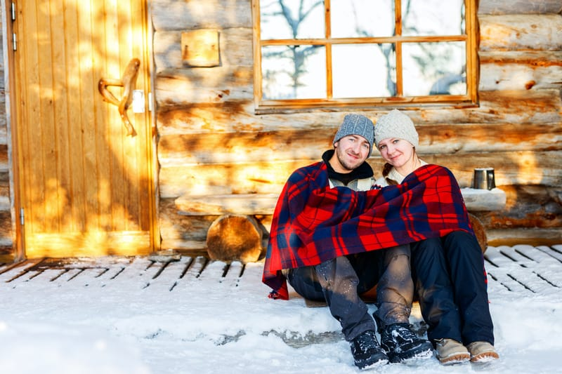 Romantic Cabins in Wisconsin, Couple outdoors on beautiful winter day in front of log cabin