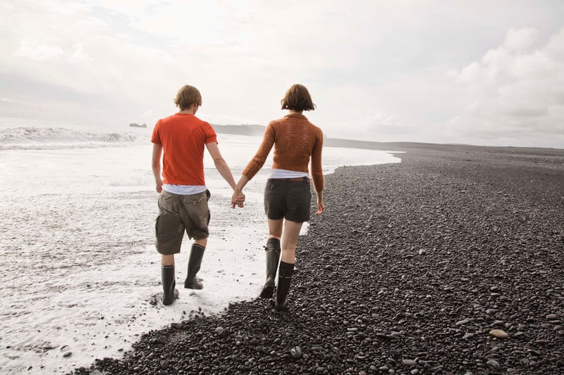 Staycation Ideas for Couples, Couple taking walk, holding hands on beach