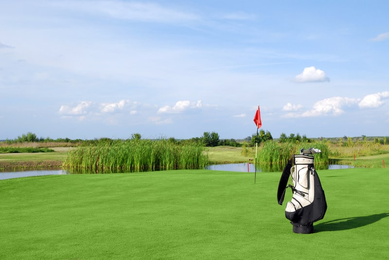 Golf field with flag and golf bag, Environmentally Friendly Golf Courses