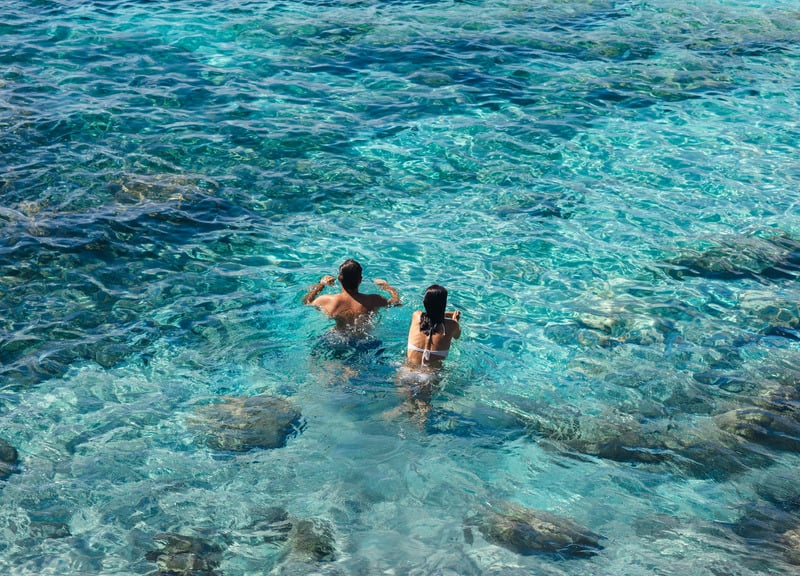 Loving staycation ideas for couples, Couple swimming in the Lake With blueish green clean water.