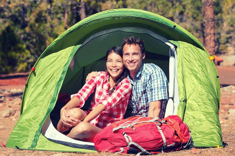 staycation ideas for couples, Happy hiking couple resting in green tent.