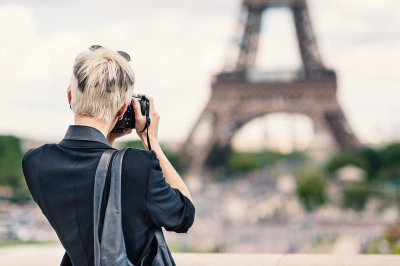 Best Staycation Ideas for Couples, Young women taking picture of eiffel tower with DSLR