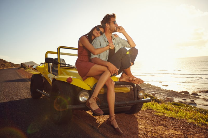 Staycation ideas for couples, Couple on a off road trip sitting on a trophy truck jeep