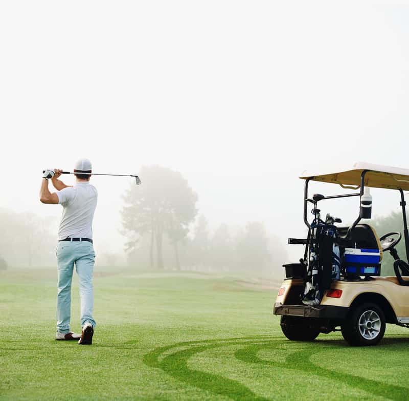 golfer in fairway with cart playing shot towards green, Environmentally Friendly Golf Courses
