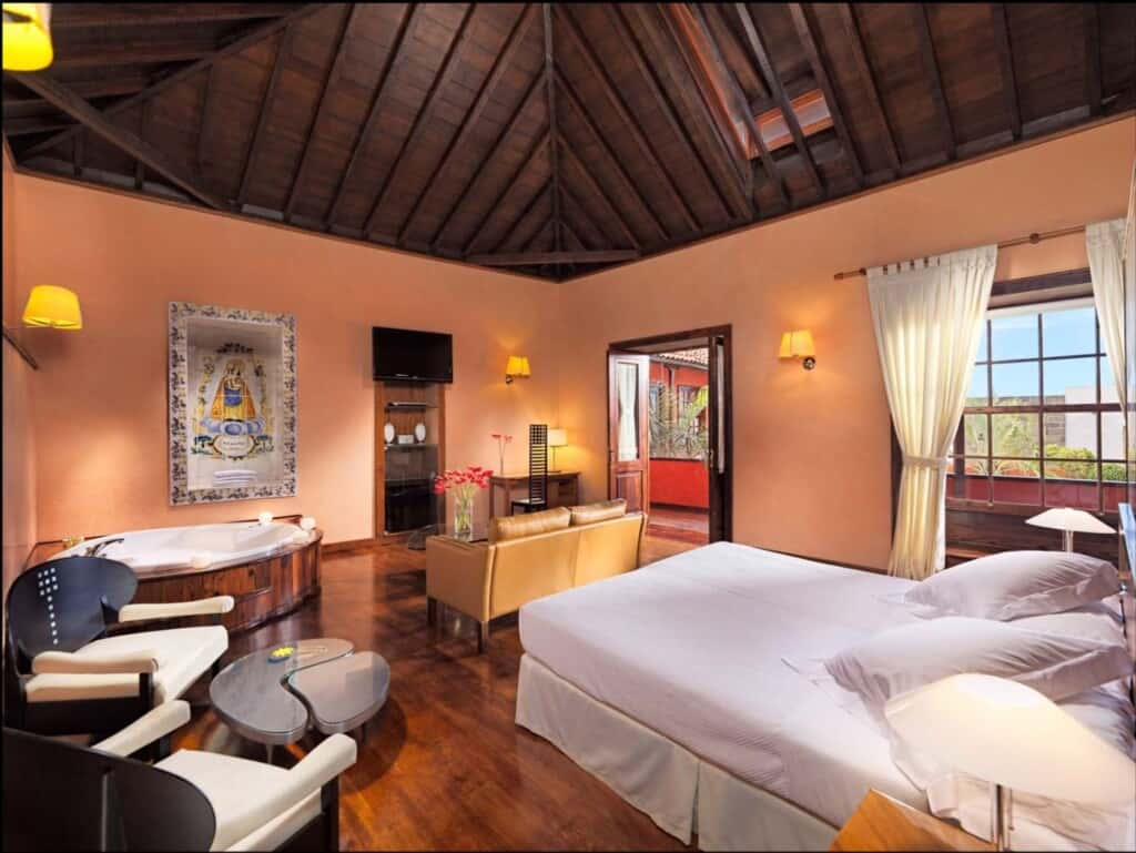 Staycation Ideas for Couples, Beautiful hotel room with comfortable bed, sofa and romantic lighting.