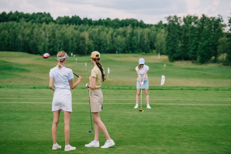 selective focus of women in caps with golf equipment looking at friend playing golf at golf course, Environmentally Friendly Golf Courses