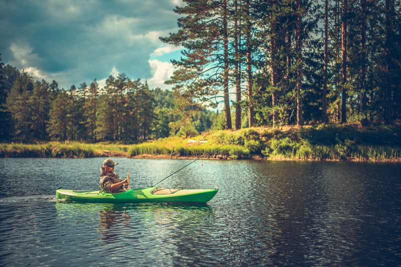 Caucasian Men in His 30s Fishing From a Kayak. Lake Recreation Time. best inflatable kayaks for fishing