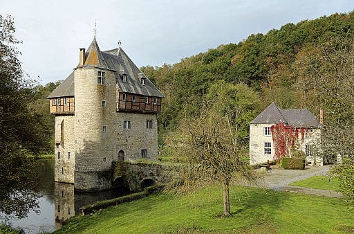 private castles in belgium, view of crupet castle in the water