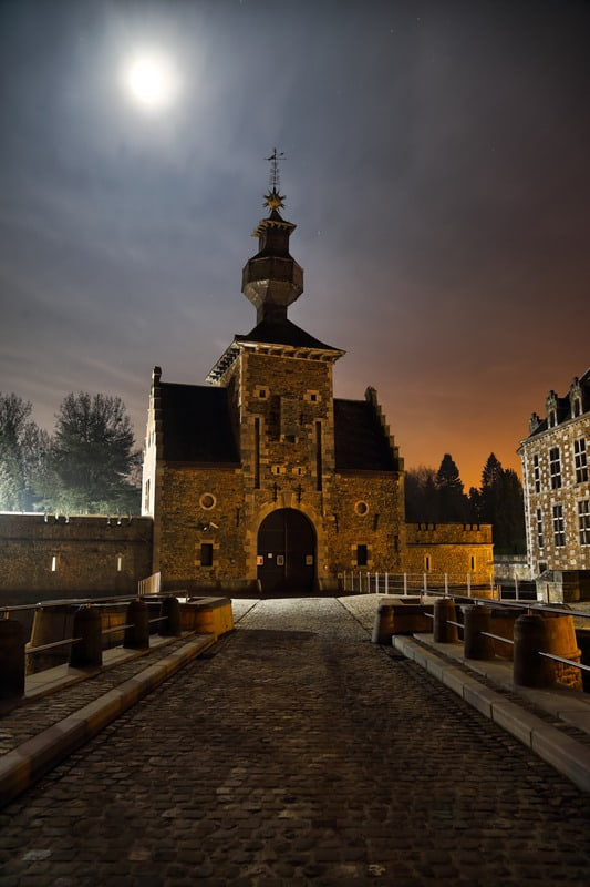 Night view of the Jehay castle in Belgium. From the entrance bridge with Full moon in the sky; beautiful castles in belgium