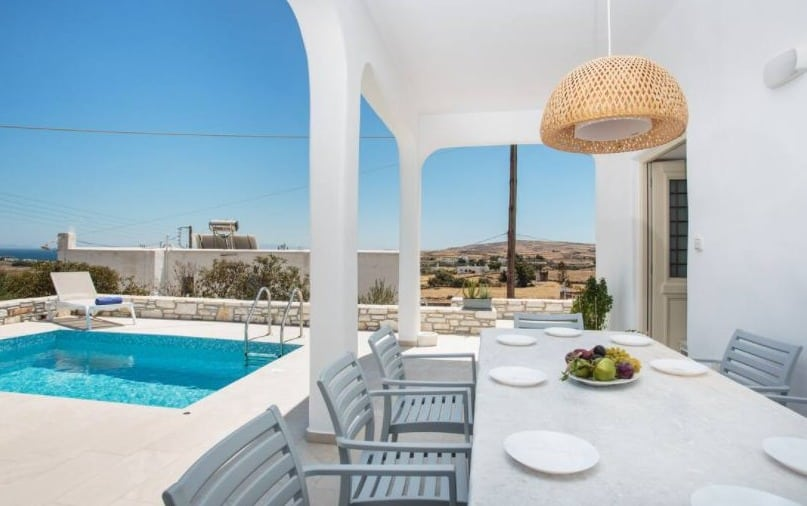 Best Villa Rentals in Paros with pool, View of pool side with dining tab in Villa Evilia