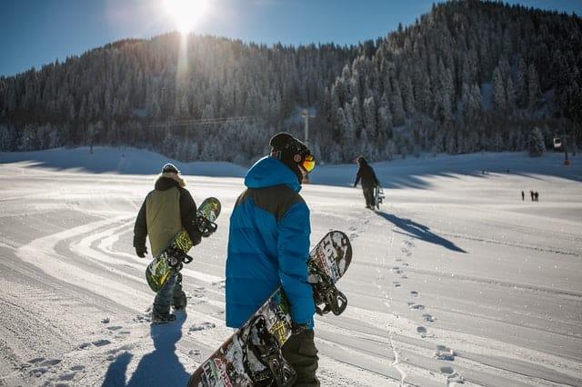 best ski resorts in Wisconsin in Devil's Head, person wearing blue winter jacket carrying snowboard under sunny sky