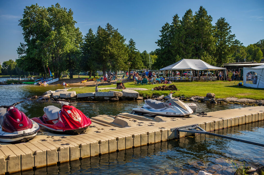 best door county resorts on the water, pier with jet skis and tent in background with lots of activity