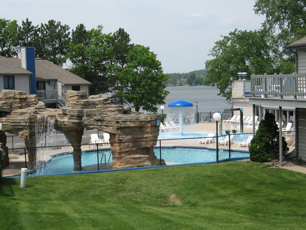 best vacation spots in wisconsin for families, view of pool area with rock formation and lake in background