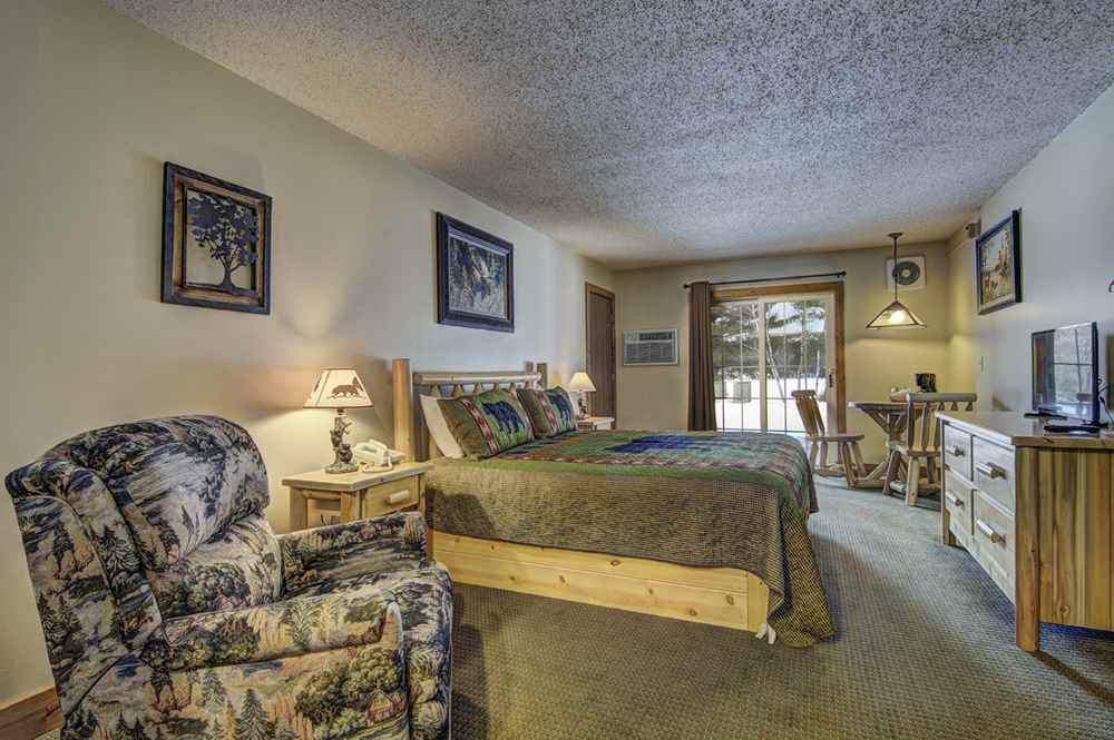 best vacation spots in wisconsin for families, sunny room with large bed and safe chair at the Eagle River Inn & Resort