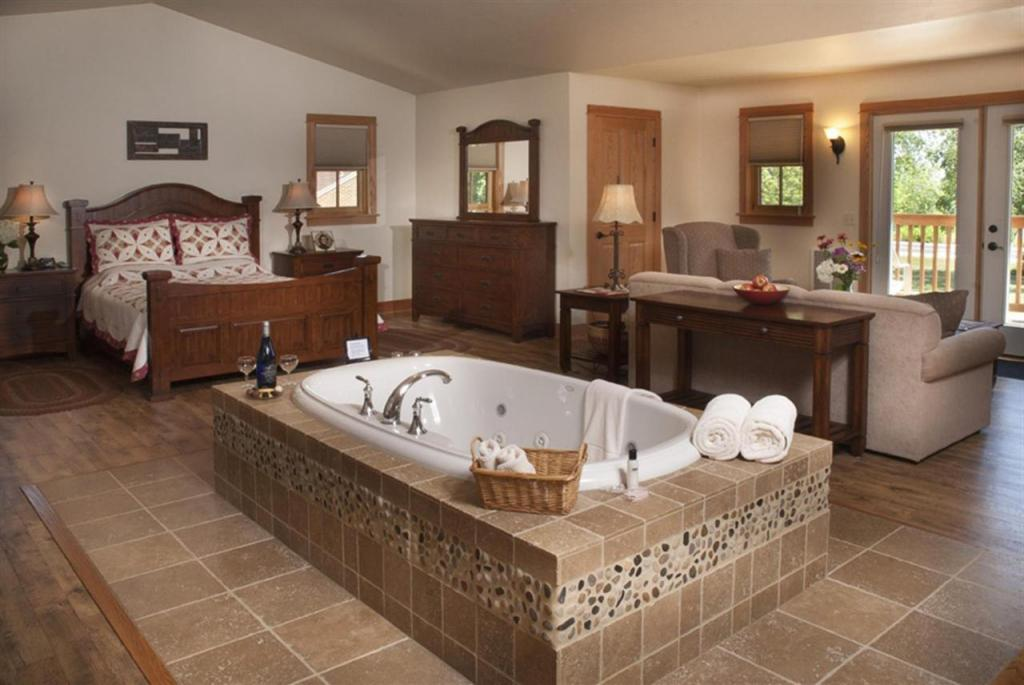 Wisconsin lake resorts for families, room with large bathtub, bed and sofa at Lake Orchard Farm Retreat
