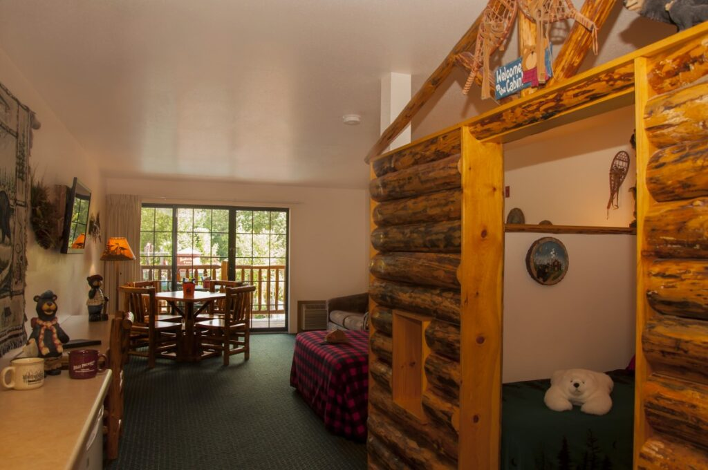 wisconsin dells kid friendly resorts, large room with bed, table, balcony and sleeping alcove for kids with bear toy