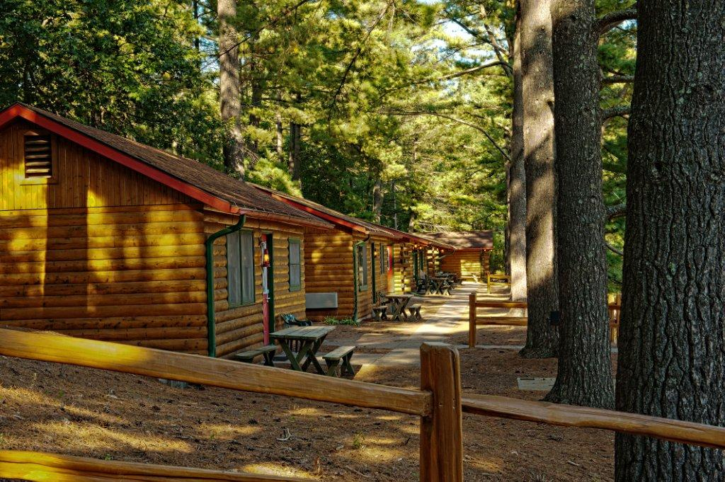 Best Family Resorts in Wisconsin, row of log cabins with outside seating area