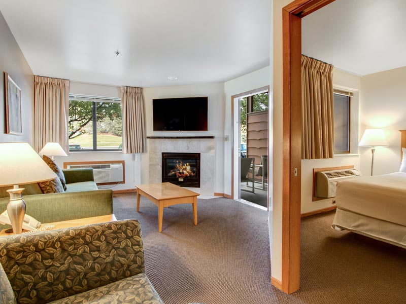resorts and spas in Wisconsin, large suite with bed, living room area with fireplace and balcony at Timber Ridge Lodge and Waterpark at Grand Geneva