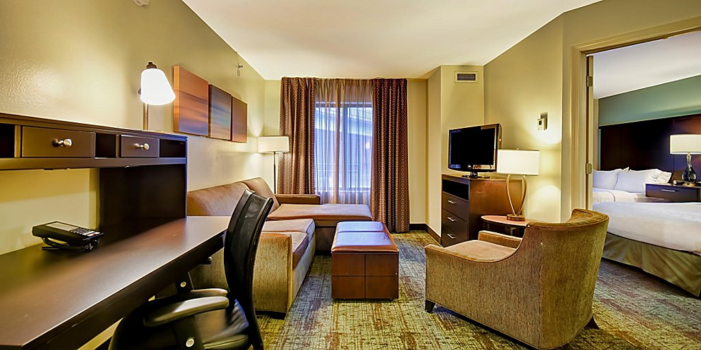 best resorts in wisconsin for families, suite with two beds,d esk and lounge area at staybridge suites