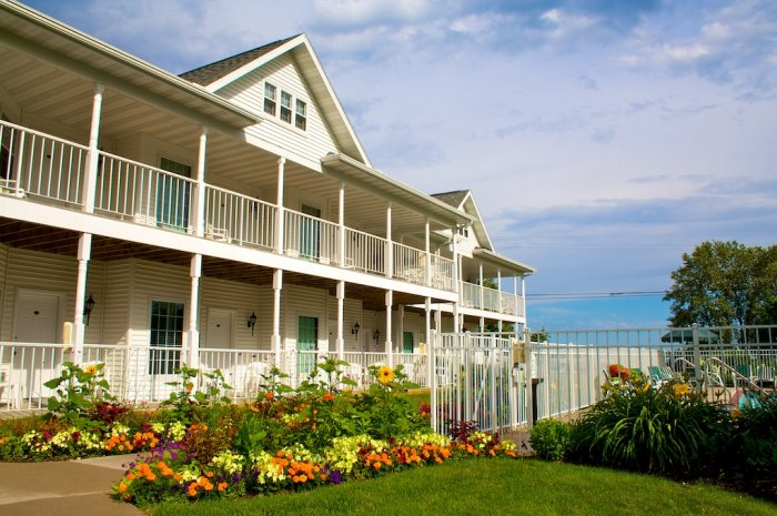 best places to stay in Door County on the water, outside of hotel with lots of flowers, pool area and lake just behind