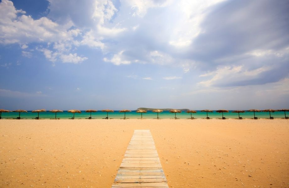 most popular beaches in Paros, wooden pathway up to row of straw umbrellas and chairs along Chrissi Akti Beach